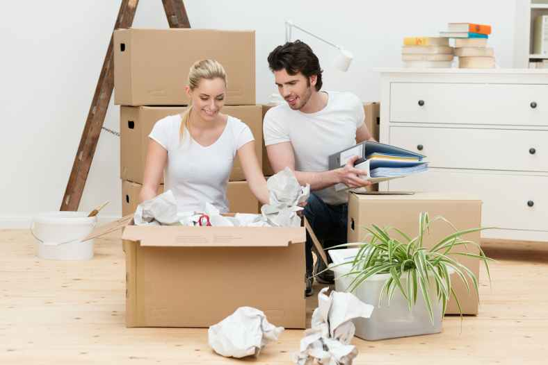 Happy young couple unpacking in their new home
