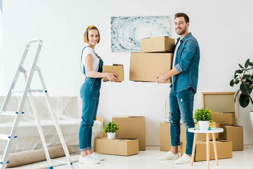 Young couple holding boxes during a house move